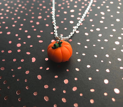 A silver necklace with a small orange and green pumpkin pendant made with modelling clay