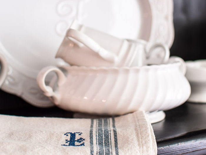 white ironstone and embroidered grain sack