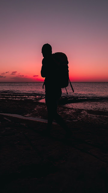 Lonely man, beach, backpack, silhouette