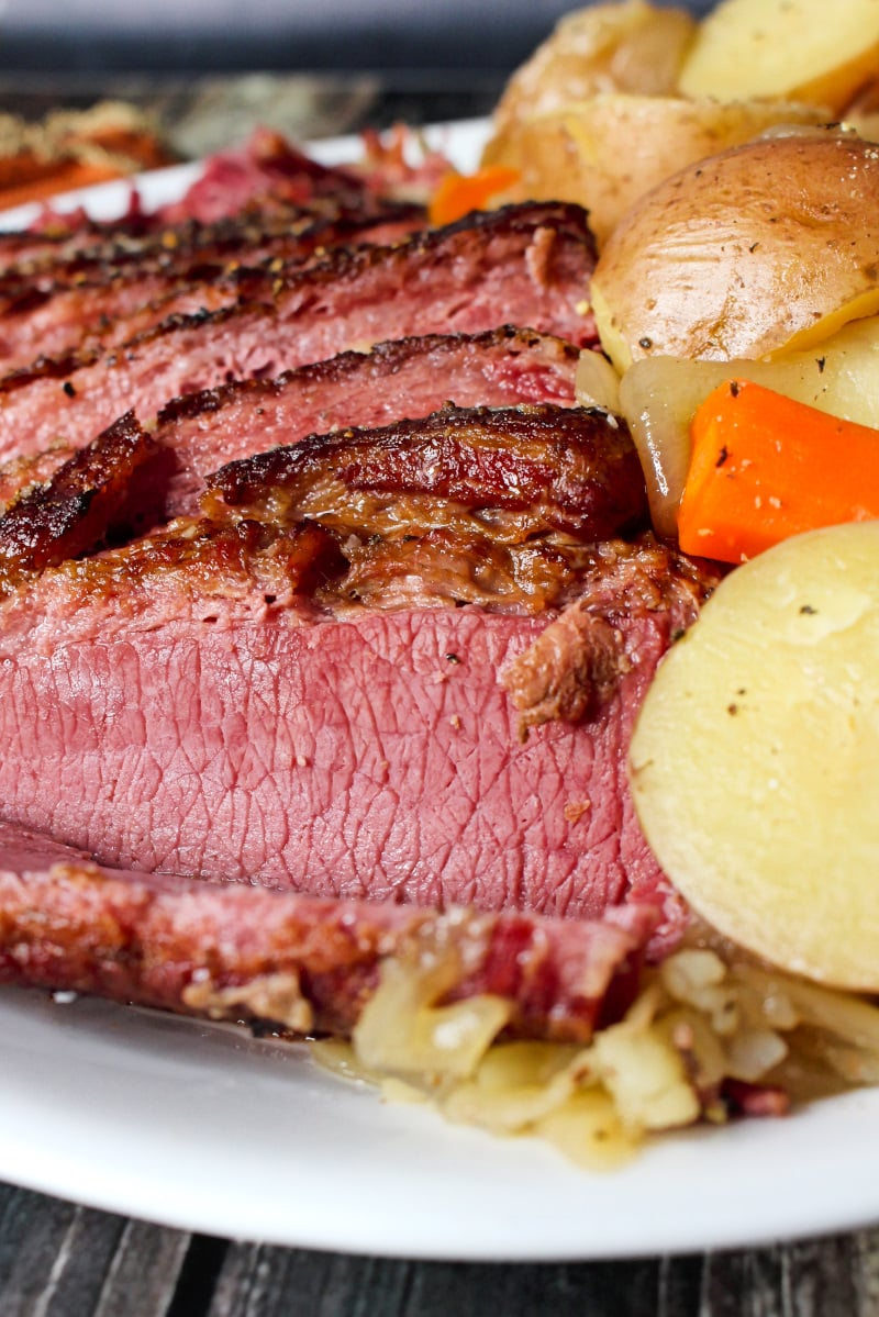 Closeup side view of sliced corned beef next to carrots and potatoes on a white plate.