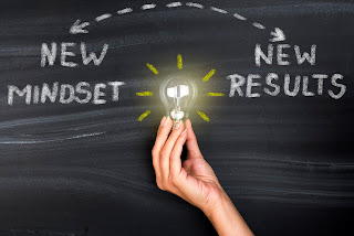 Hand holding up lightbulb in front of chalkboard reading 'New Mindset, New Results'