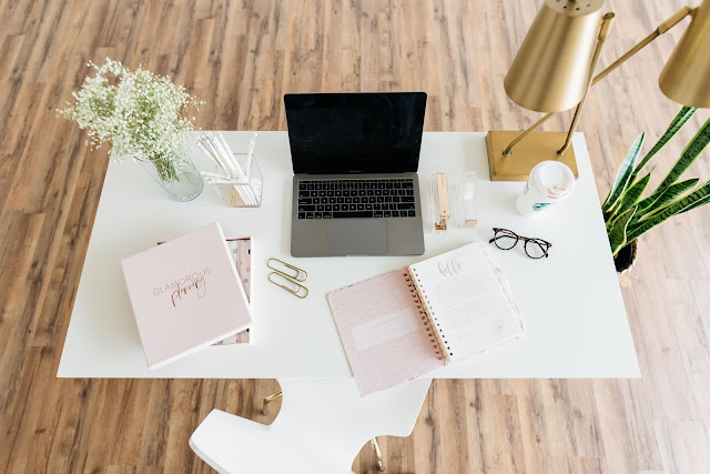 This is an office with a white desk on wooden floors. There is a white chair pulled up to the desk. On the desk is a vase wtih white flowers, a laptop, multiple notebooks and statiornay. There is also a coffee cup and a pair of glasses next to the laptop