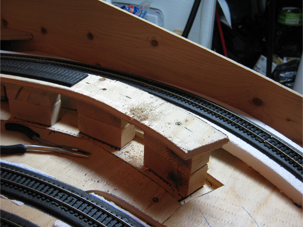 Before photo of an original section of benchwork leading up to a wooden train trestle