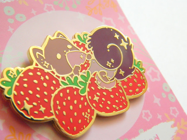 A photo of a pin badge, a squirrel surrounded by strawberries. the pin has a shiny gold outline