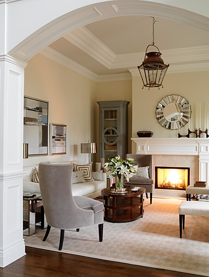 Elegant neutral living room with arched wood paneled entrance by Sarah Richardson