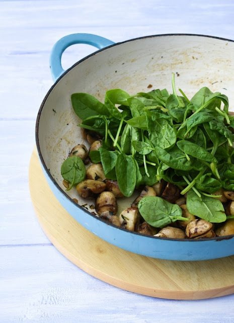 sauteed garlic mushrooms and spinach in a white cast iron frying pan