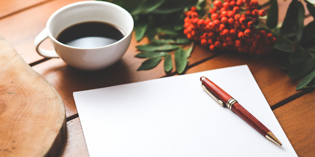 An image of a coffee cup next to some flowers and a pad with a red pen lying on top.
