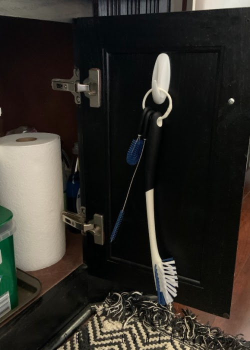Organizing at home by using command hooks for scrub brush under the sink