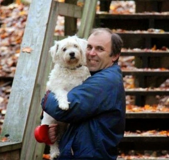A photograph of Brad Roth holding his dog Suki Roth in Michigan's fall color.