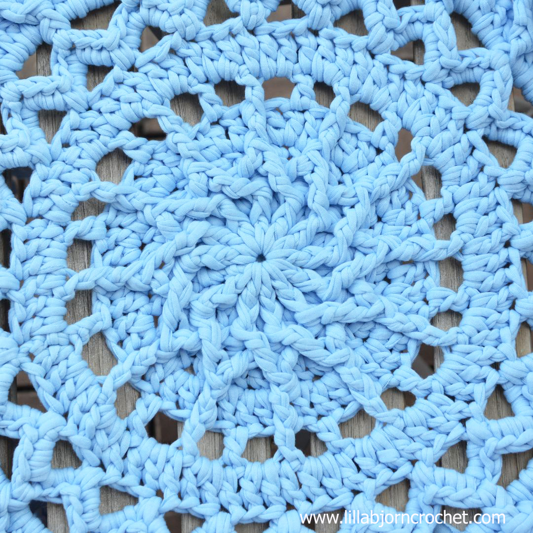 Andromeda Mandala Rug combines textured stitches with open, lace parts. The pattern can also be used for a doily when lighter yarns and small hook are used. Original design by Lilla Bjorn Crochet.