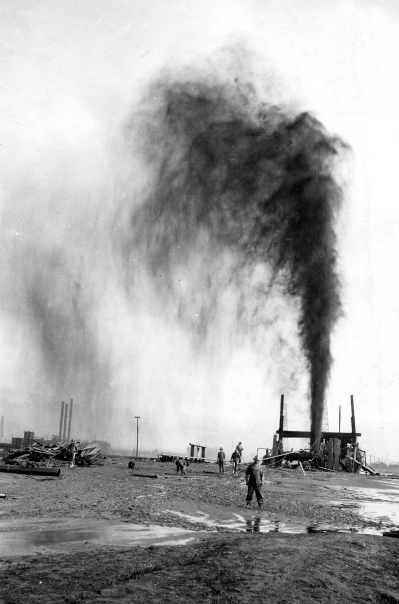 A worker poses in front of the runaway oil well.