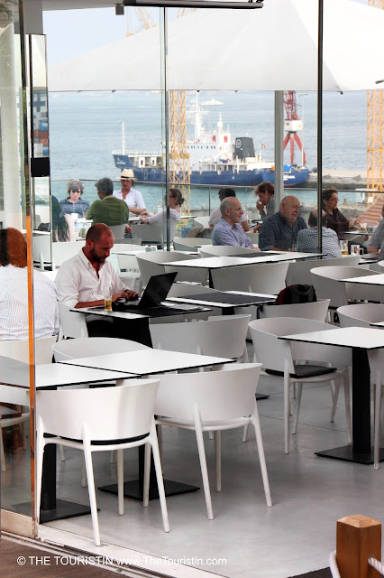 People sitting in a white decorated cafe with a harbour and ships in the distance.