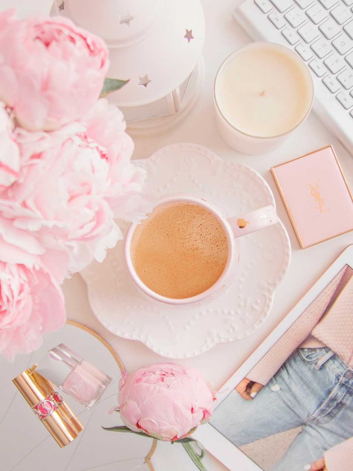 A cup of tea surrounded by pink flowers and candles