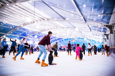 Blue Martini Ice Rink with families skating in large tunnel shaped building