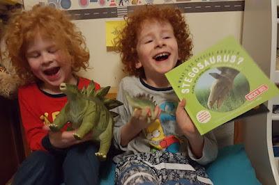Stegosaurus toys and book children laugh