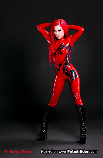 Red latex catsuit Amy Grey has red hair and long black PVC boots