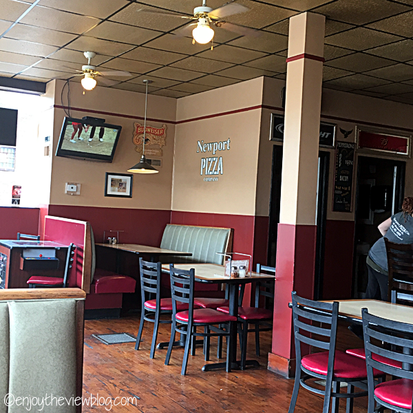 inside Newport Pizza Company - cream upper walls, dark red lower walls, booths and tables and chairs, TV on the wall