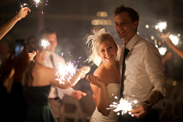 bride and groom with sparklers inside a building and surrounded by smoke