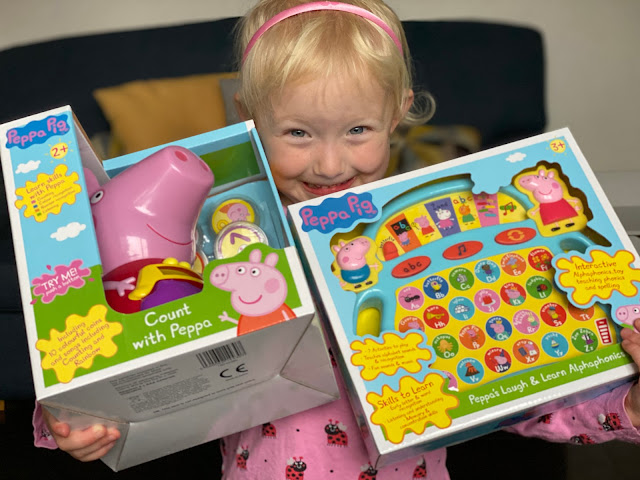 A very happy looking 3 year old holding 2 Peppa Pig toys in their boxes before reviewing them