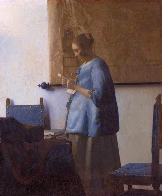 Femeie citind o scrisoare la fereastră