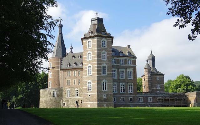 Schloss Merode mit Wald und braunen Schlossmauern und grünen Wiesen im Rheinland