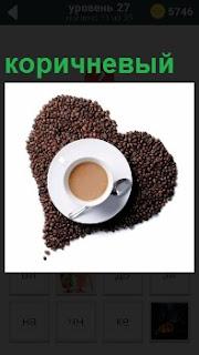 На столе из кофейных коричневых зерен выложено сердце и в середине находится чашка с кофе