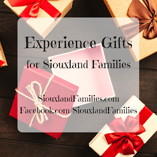 "red and white packages tied with ribbons surround an open, empty gift box in the background. In the foreground, the words ""Experience Gifts for Siouxland Families"""
