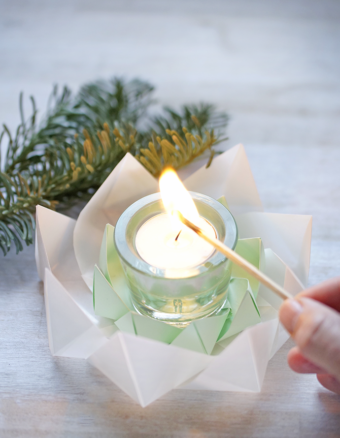 Ein Teelicht anzünden mit einem Strechholz in einem Tangramistern