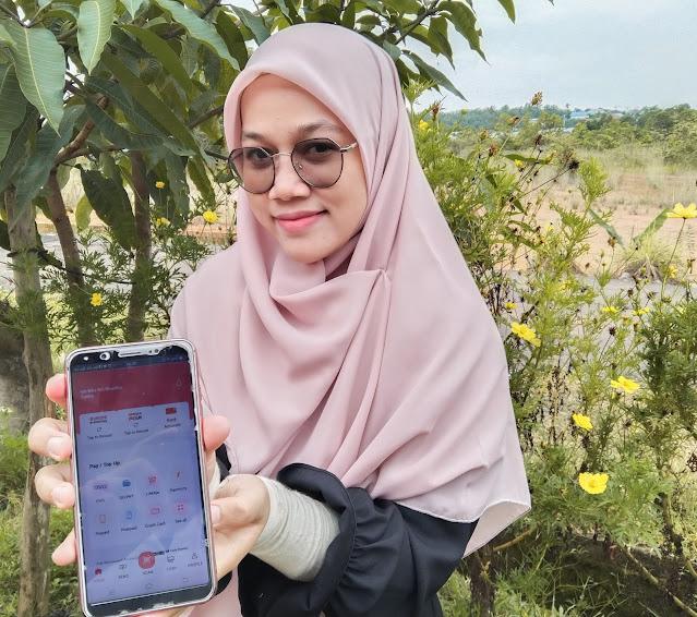 perempuan menunjukkan aplikasi tabungan online simobiplus