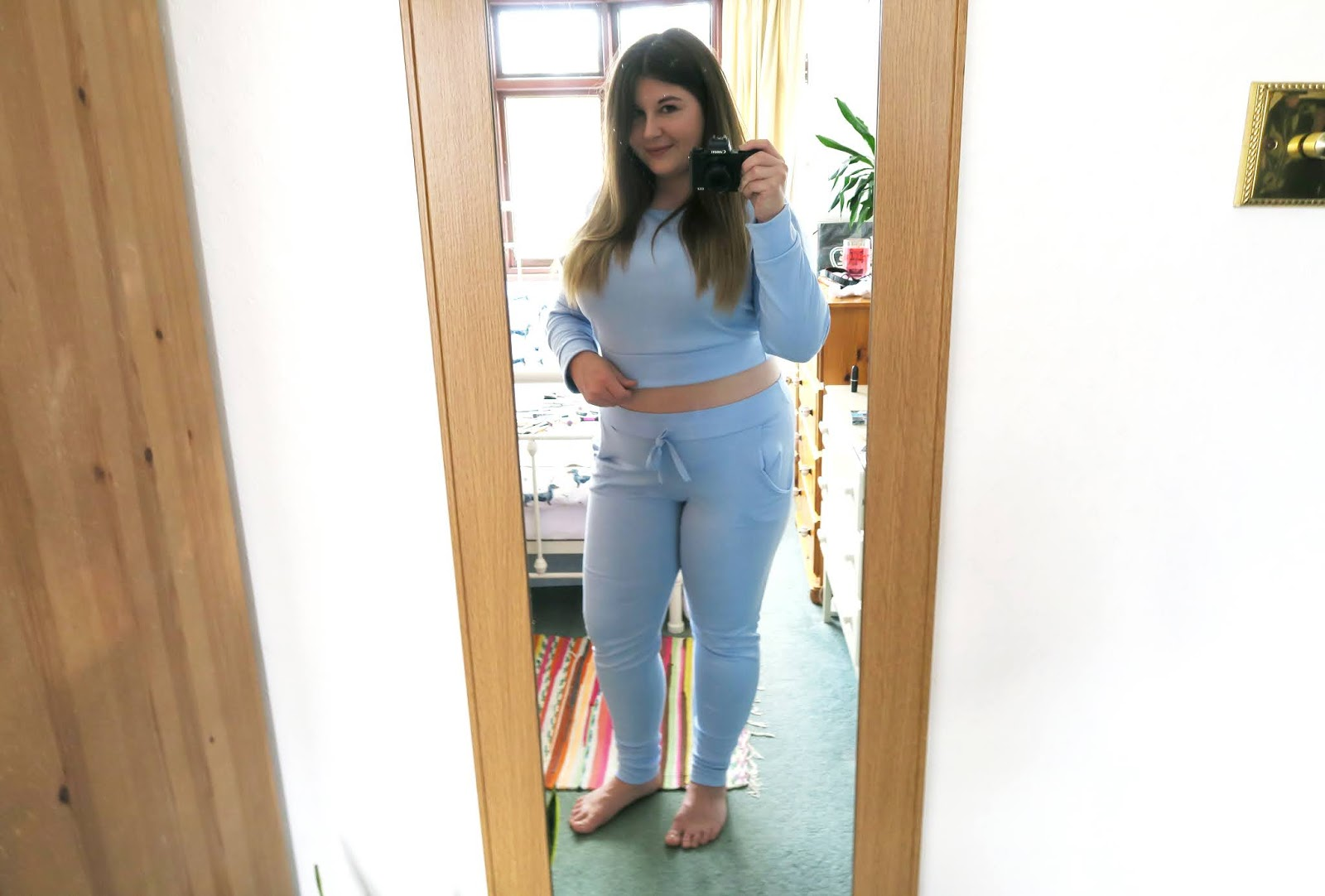 Grace can be seen posing in a full length mirror wearing a baby blue loungewear set. Her stomach is on show.