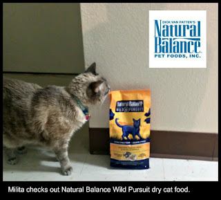 Milita is in the kitchen checking out a bag of Natural Balance Wild Pursuit dry cat food.