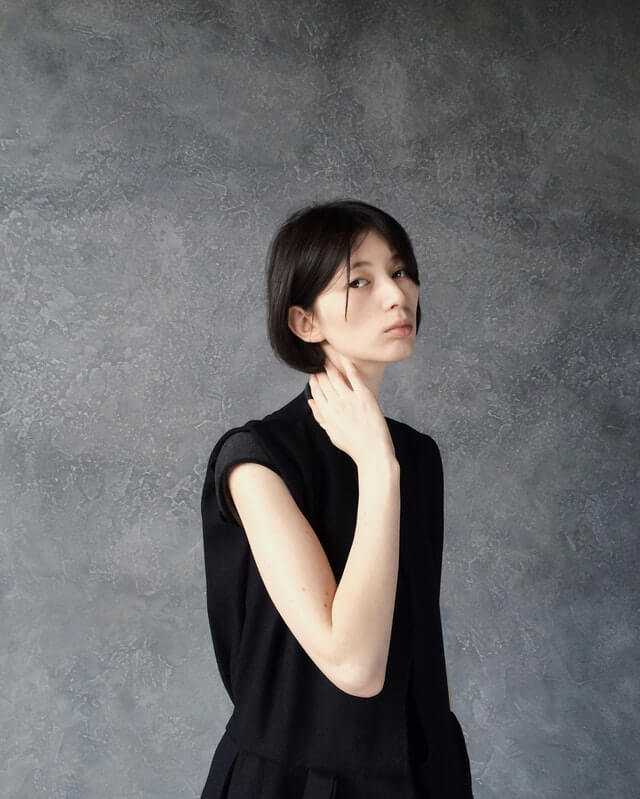 Woman-in-Black-Top-Standing-Near-Gray-Wall