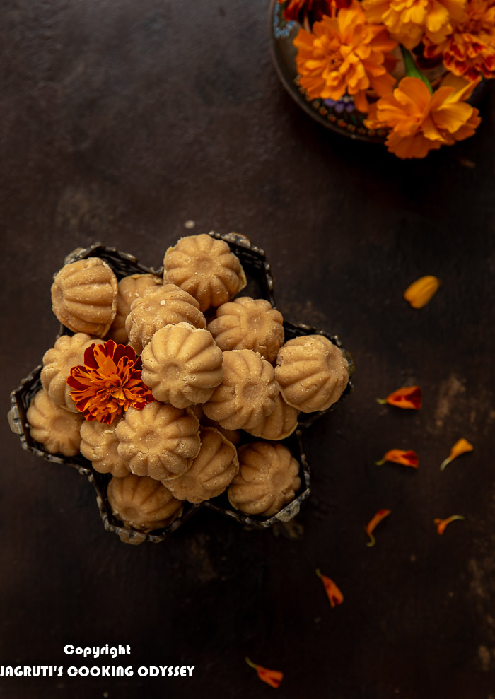 Overhead shot of Mawa peda placed in a metal bowl with marigold flower next to bunch of flowers and petals.