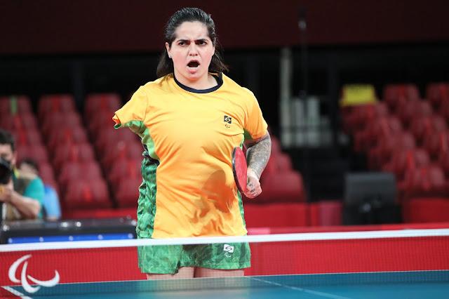 A mesatenista Bruna Alexandre, que não tem o braço direito, comemora um ponto. Ela está de boa aberta e aparenta euforia, inclusive franzindo a testa. Ela está com uniforme da seleção com a camisa amarela na frente e verde do lado.
