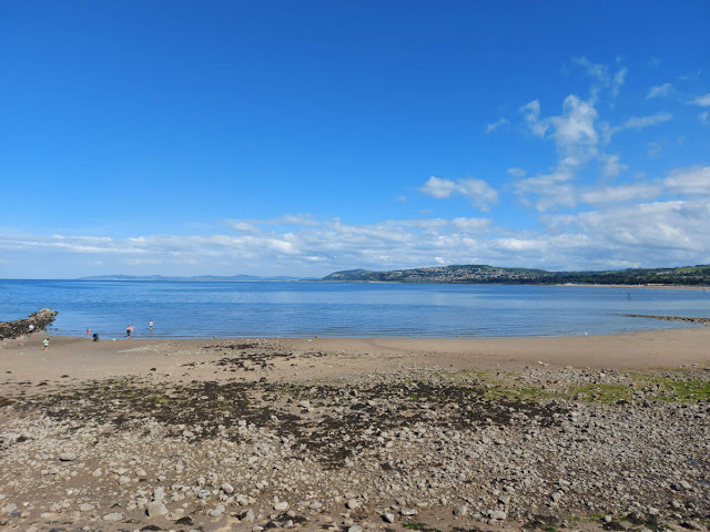 A view across a sand and pebble beach to the sea.  The tide has gone out.