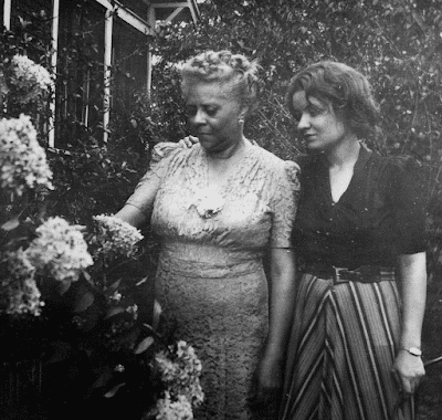 An undated photograph of Florence Price in later life with her daughter Florence Louise Robinson looking at flowers in an outdoor garden (University of Arkansas Libraries)