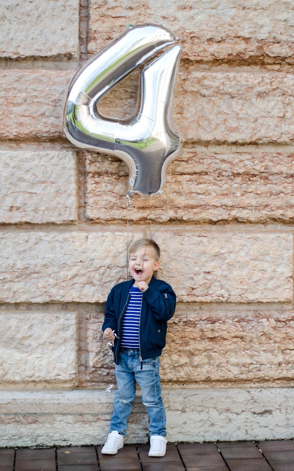 toddler boy with number 4 silver foil balloon