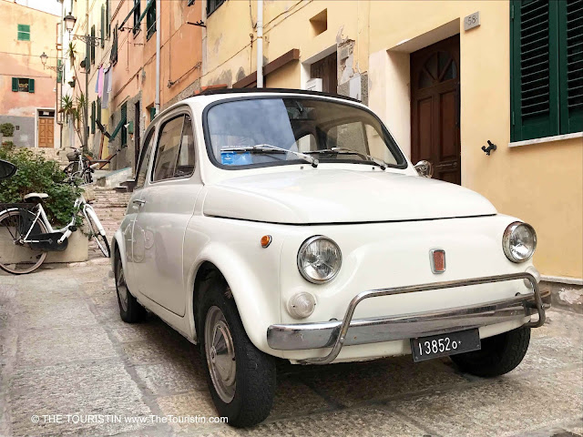 A white classic Fiat 500 parked on a narrow lane lined by pastel-coloured houses.