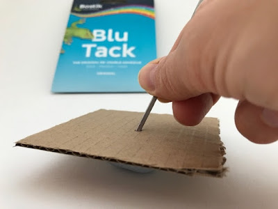 Blu Tack being used to help make a hole in cardboard