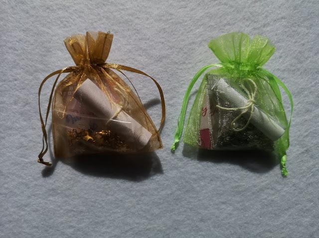 Catenine nella confezione: sacchetto di organza colorato, bigliettino da visita e mini-pergamena con spiegazione
