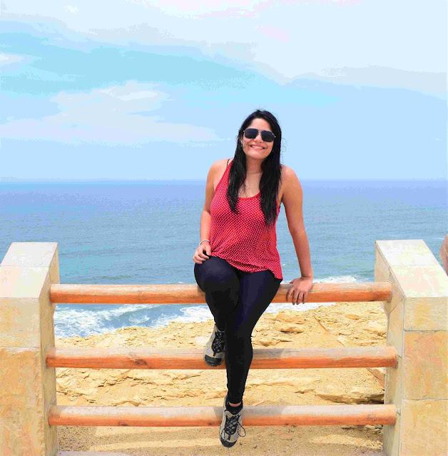 mulher sentada em uma mureta de um mirante do mar