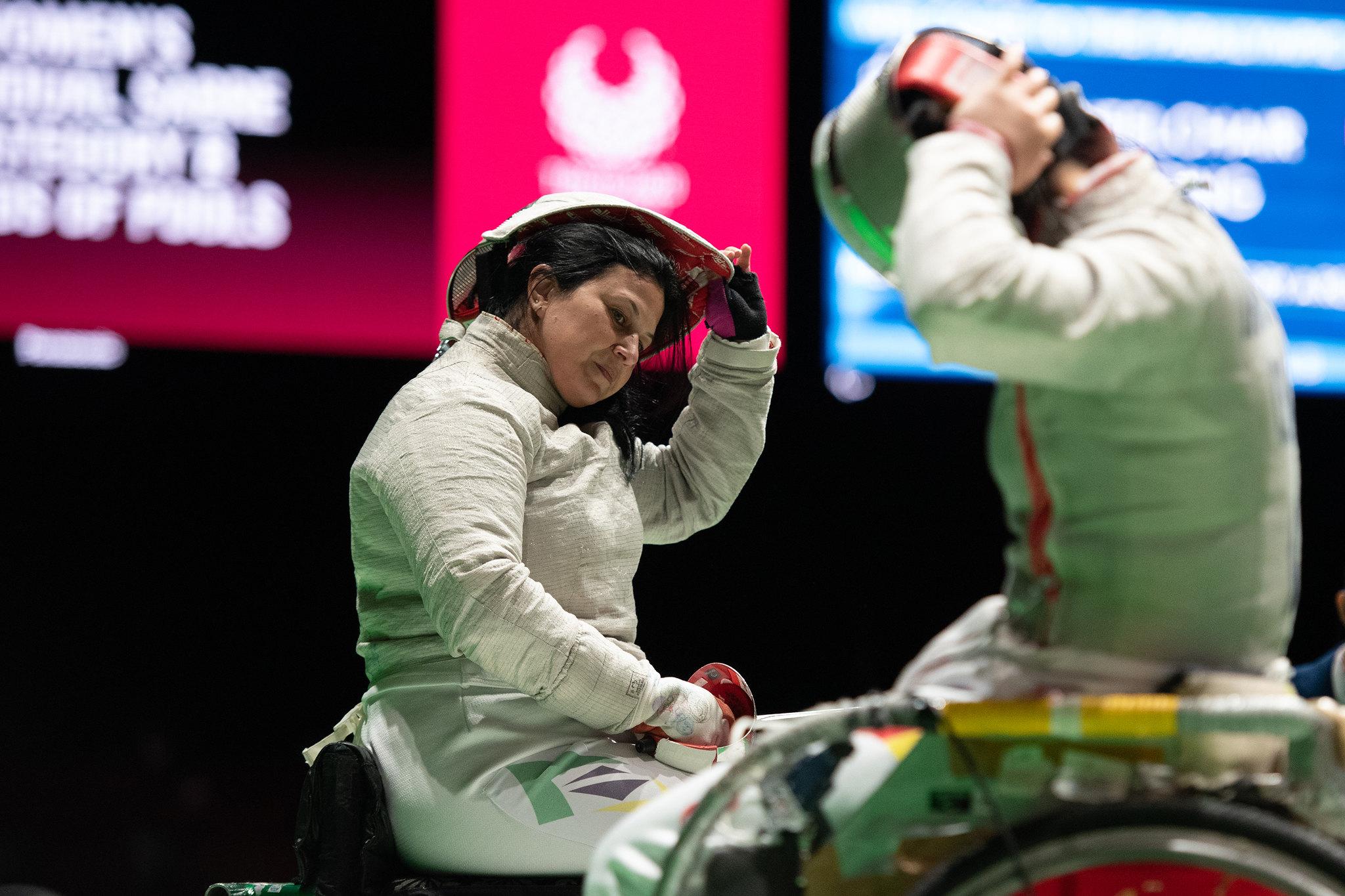 De uniforme, Monica Santos retira máscara de esgrima em cadeira de rodas