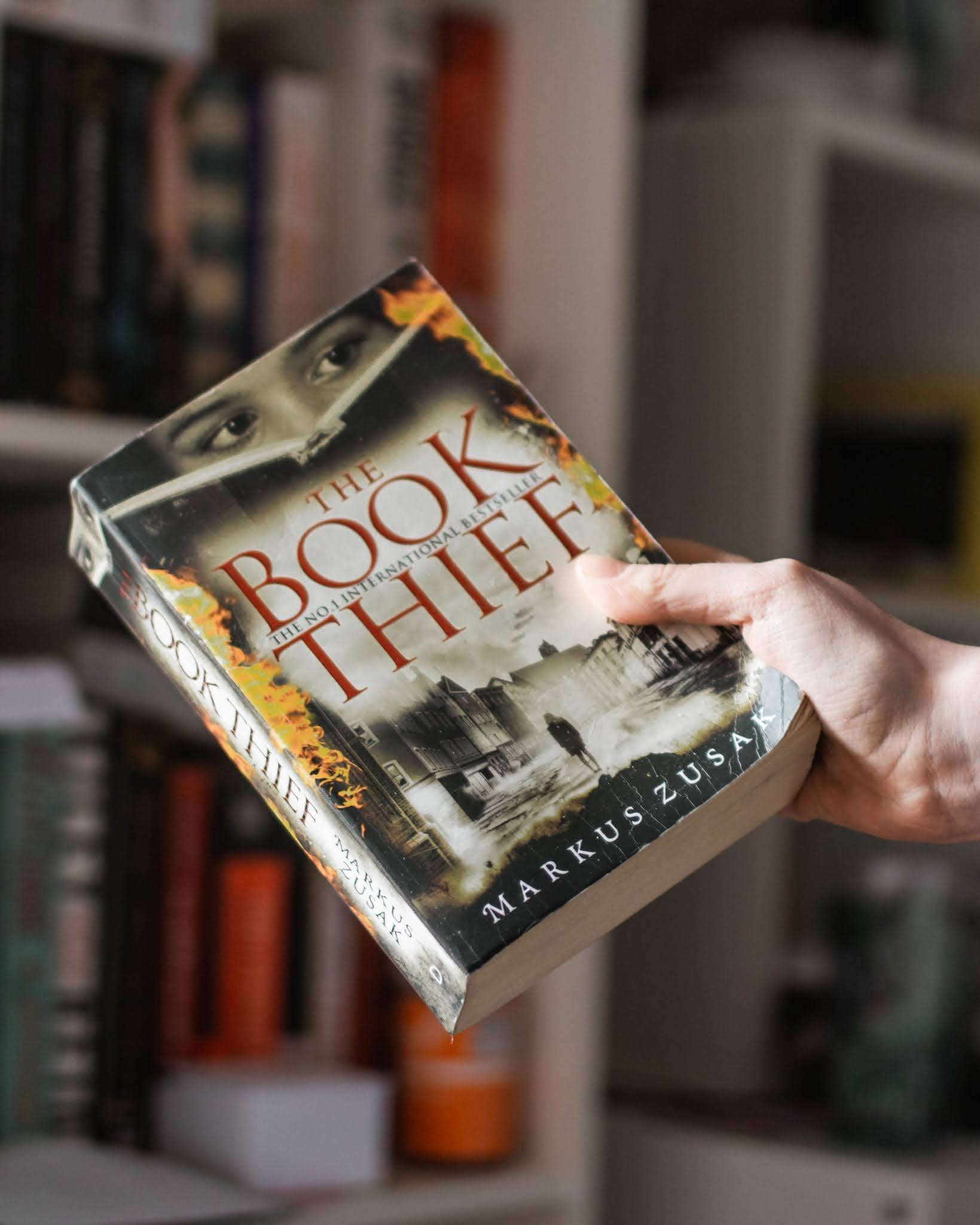 hand holding the book thief by markus zusak in front of bookcase