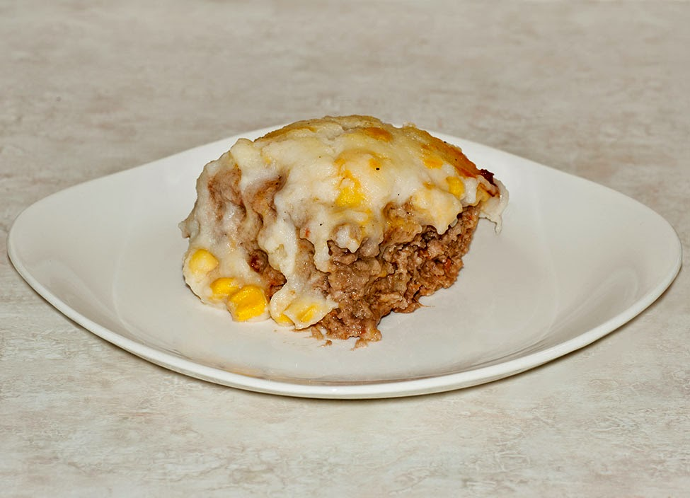 A slice of shepherd's pie on a plate, ready to serve.