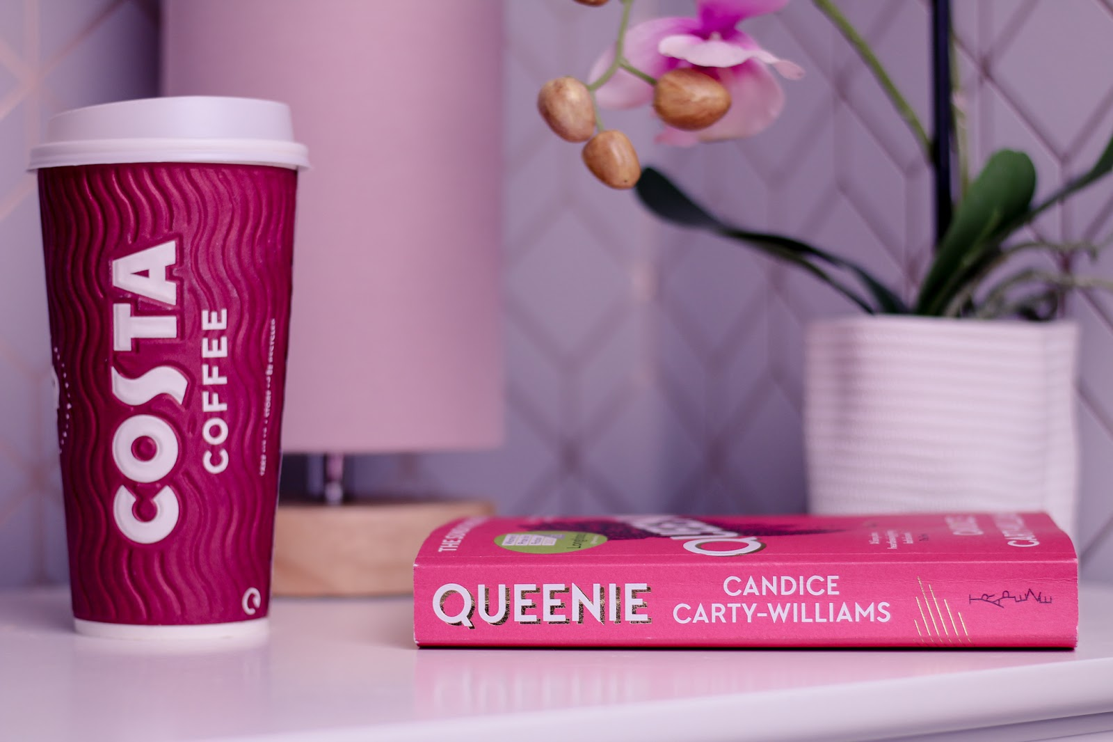 Close up photo of the book Queenie by Candice Carty-Williams on a white bedside table next to a Costa take away cup