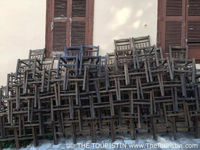 Large amount of stacked brown wooden chairs at a taverna in Athens in Greece