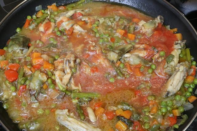 Arroz con pollo y verduras cocinandose