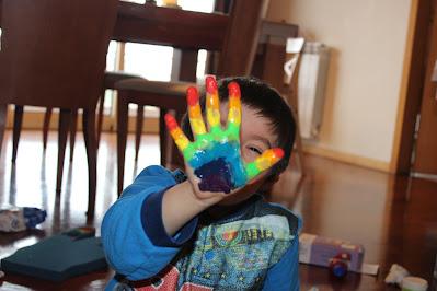 Criança com as mãos pintadas com tinta para fazer um arco-íris