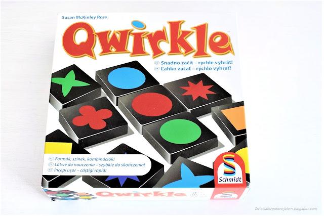 na zdjęciu opakowanie gry qwirkle, duże, kwadratowe, z czerwonym napisem i ilustracja kolorowych klocków - elementów gry