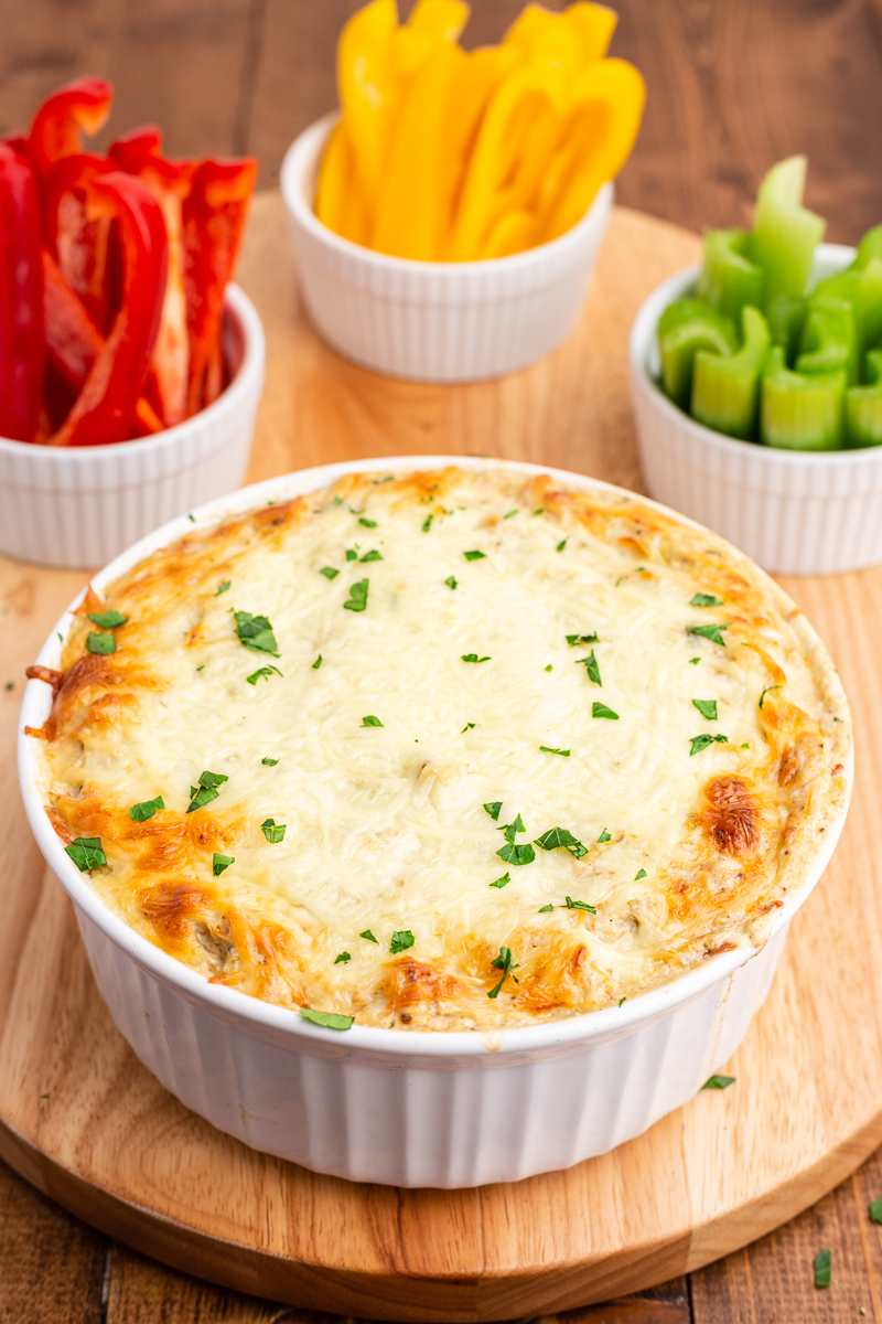 Photo of completed Low Carb Artichoke Crab Dip in a white bowl on a wooden cutting board with bell pepper slices.